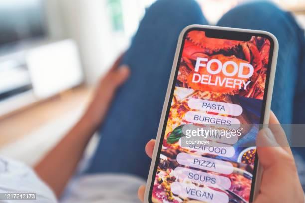 frau hält ein mobiltelefon mit einem essen sendemenü darauf. - bucht stock-fotos und bilder