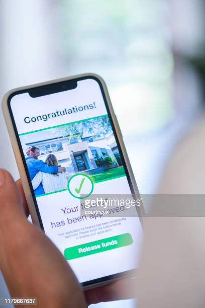 woman holding a mobile phone with loan application approval. - representing stock pictures, royalty-free photos & images