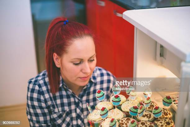 Woman holding a muffins in her hands, body in background, Easter food, green color, muffin isolated/ Muffin in woman' s palms