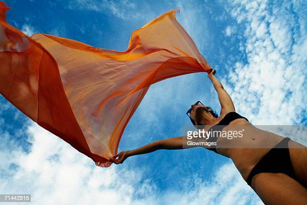 woman holding a orange colored fabric in the tropical breeze on the island of barbados, caribbean - flasher stock photos and pictures