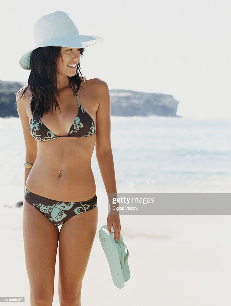 3617445c0d413d Woman Holding a Pair of Flip Flops and Wearing a Bikini and Straw Hat  Walking at