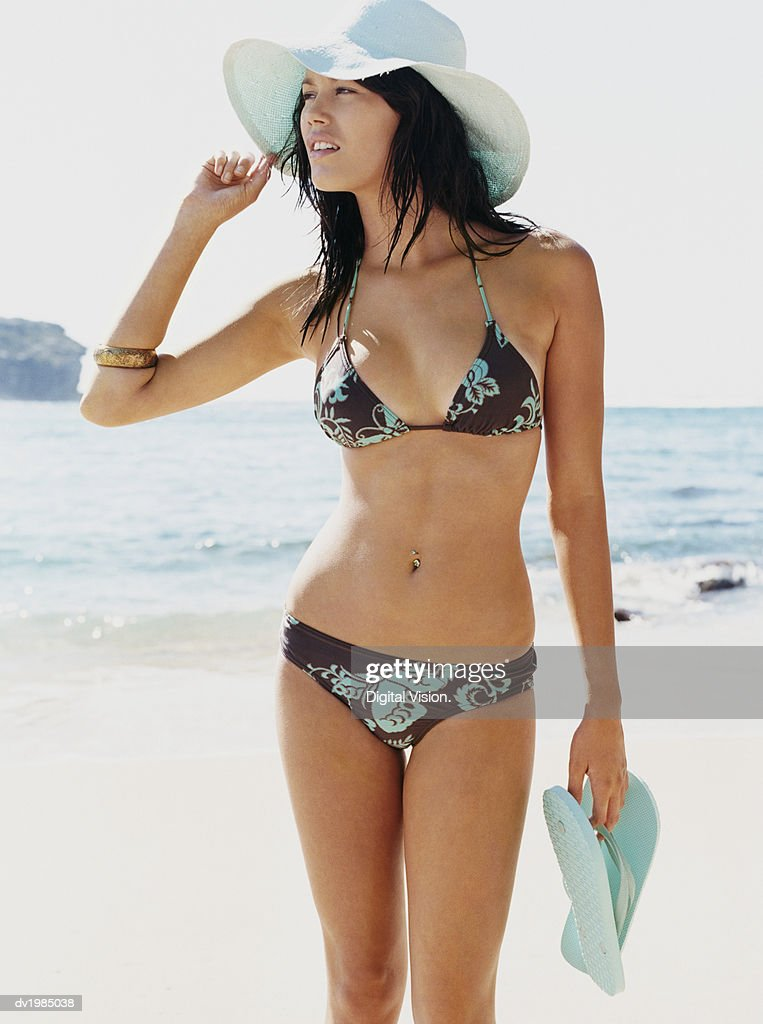 Woman Holding a Pair of Flip Flops and Wearing a Bikini and Straw Hat Walking at Water's Edge : Stock Photo
