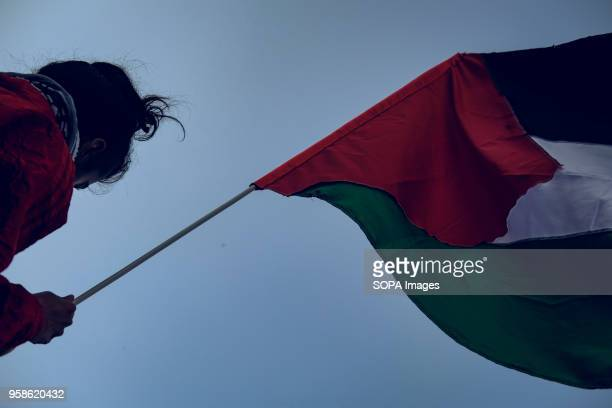 A woman holding a Palestinian flag at the protest in Berlin against the actions of Israel in Gaza where over 50 been have been killed Hundreds of...