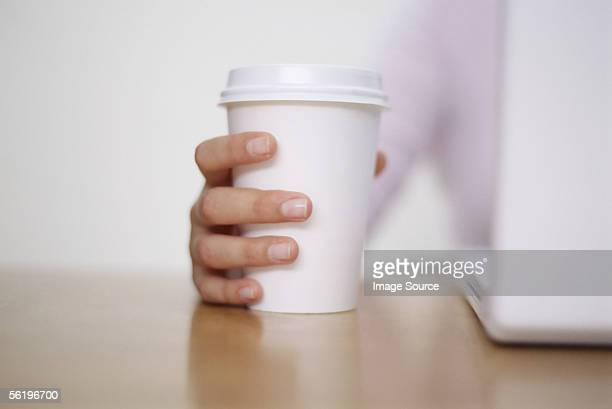 Woman holding a paper coffee cup