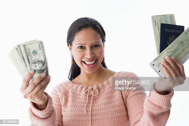 A woman holding a passport airplane tickets and dollars