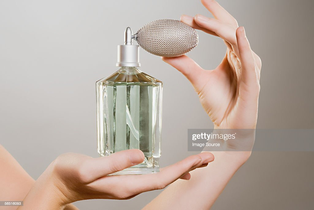 Woman holding a perfume bottle : Stock Photo