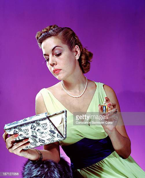 Woman holding a perfume bottle while looking into her clutch purse, New York City, 1943.