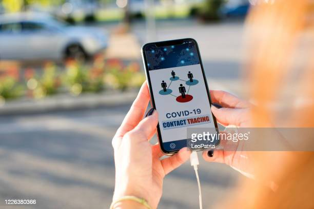 woman holding a phone in the street using the contact tracing app - contact tracing stock pictures, royalty-free photos & images