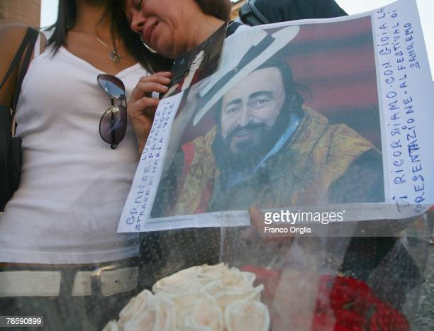 A woman holding a picture of Luciano Pavarotti cry at Luciano Pavarotti's funeral The service was held in Modena's Duomo on September 8 2007 in...