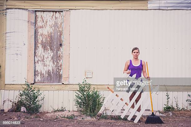 Woman holding a piece of a fence and a broom
