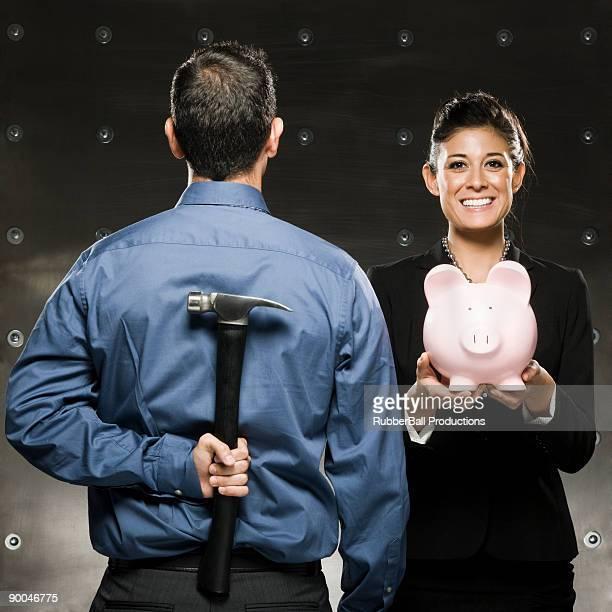 Frau hält ein Sparschwein und ein Mann mit einem hammer hinter seinem