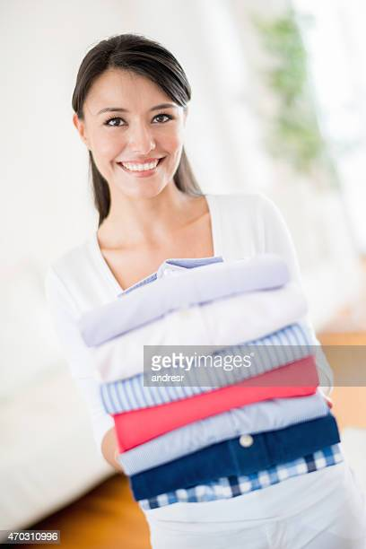 Woman holding a pile of ironed clothes