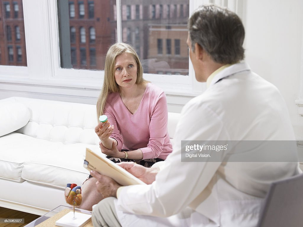 Woman Holding a Pill Bottle and Listening to Her Physician's Explanations : Stock Photo