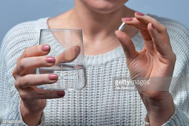 woman holding a pill. - painkiller stock pictures, royalty-free photos & images