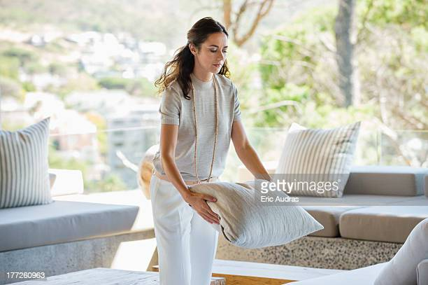 woman holding a pillow at home - cushion stock photos and pictures