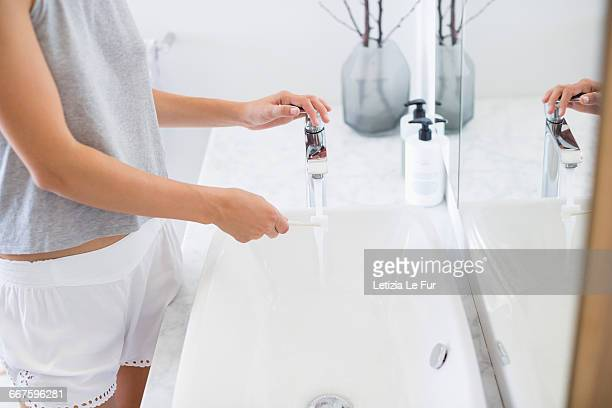 Woman holding a pink toothbrush with toothpaste on top under a running tap