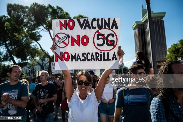 Woman holding a placard against the use of vaccine and 5G, and people without wearing face masks protesting during a demonstration against the...