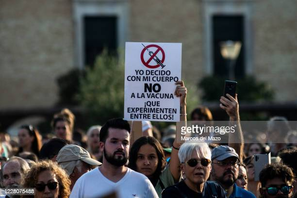 Woman holding a placard against the use of vaccine and people without wearing face masks protesting during a demonstration against the mandatory use...