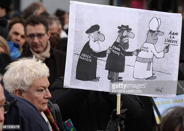 A woman holding a placard depecting a cartoon representing a priest a imam and a rabbi reading attends a Unity rally Marche Republicaine on January...