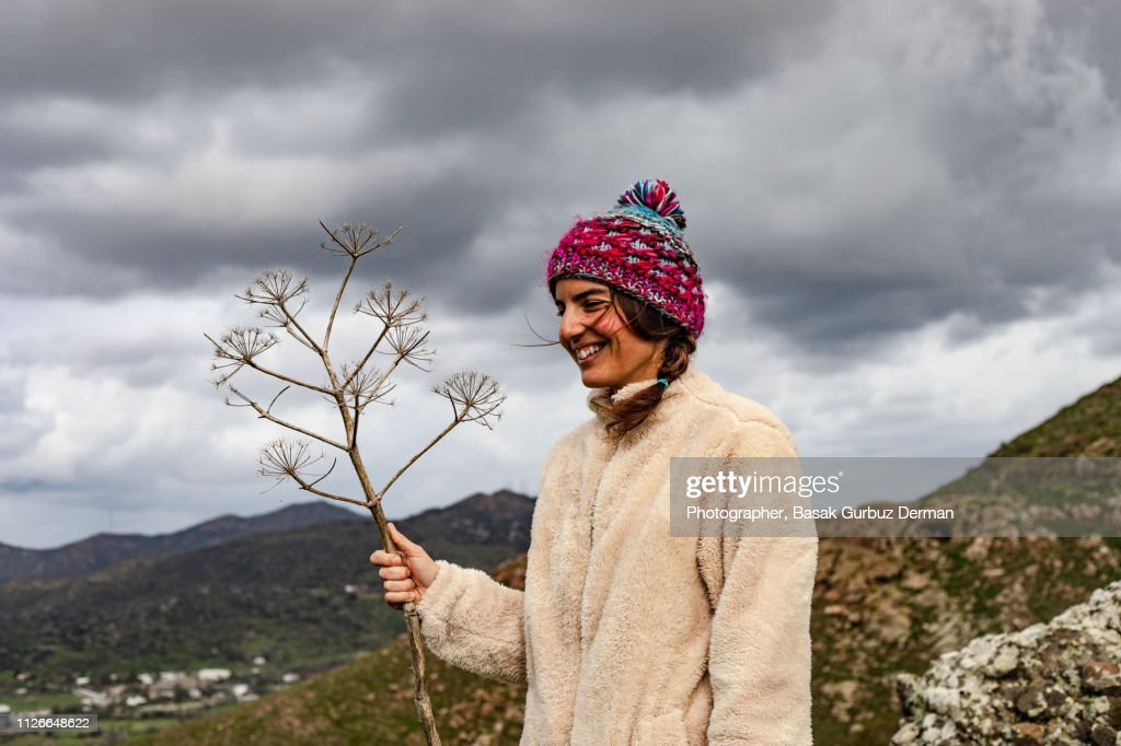 A Woman Holding A Plant In Rocky Hills Wearing Outdoor