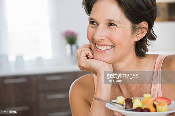Woman holding a plate of fruit salad