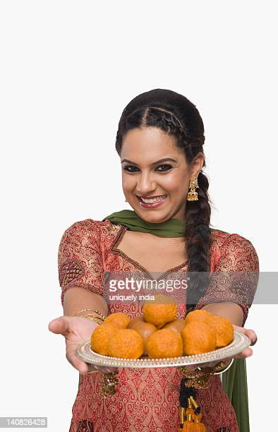 Woman holding a plate of laddu