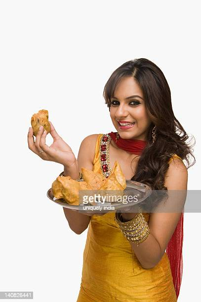 Woman holding a plate of samosa the traditional Indian snack