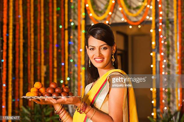 woman holding a plate of sweets on diwali - diwali sweets stock photos and pictures