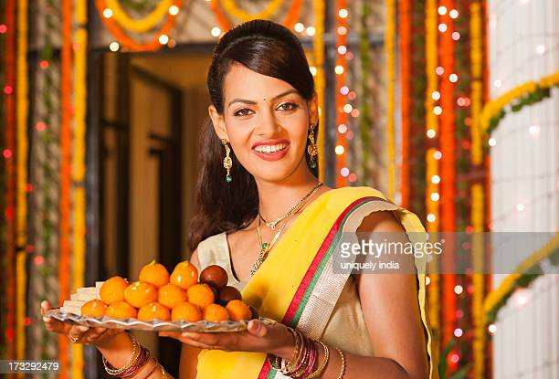 Woman holding a plate of sweets on Diwali