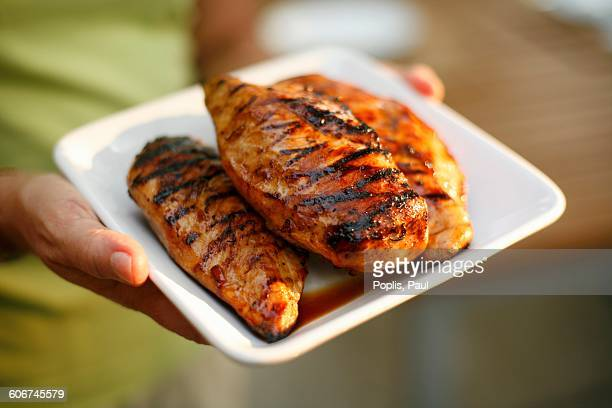 Woman Holding a Platter with Three Grilled Chicken Breasts