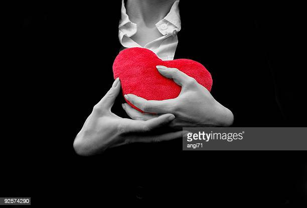 A woman holding a plush red heart