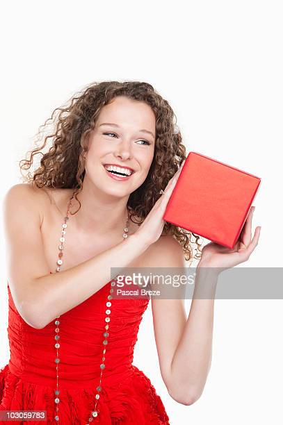 woman holding a present near her ear - shaking stock pictures, royalty-free photos & images