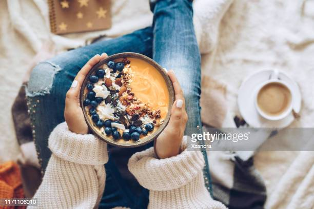 woman holding a pumpkin smoothie bowl - nut food stock pictures, royalty-free photos & images