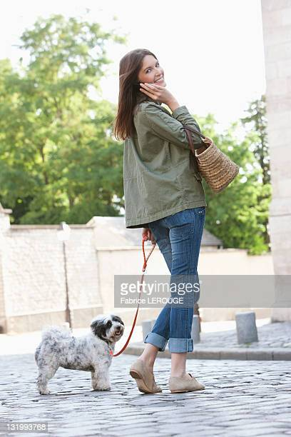 Woman holding a puppy on leash while talking on a mobile phone, Paris, Ile-de-France, France