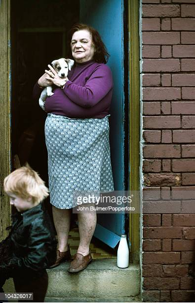A woman holding a puppy stands in a doorway in Salford Greater Manchester in 1976
