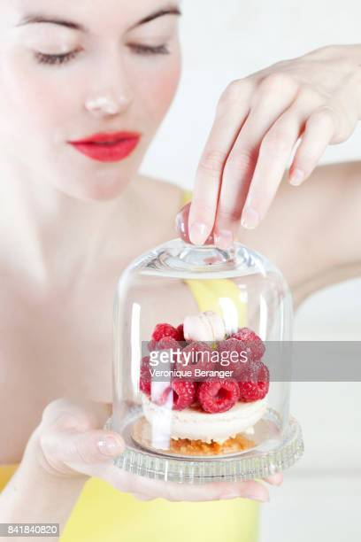 woman holding a raspberries cake under a bell jar. - temptation stock pictures, royalty-free photos & images