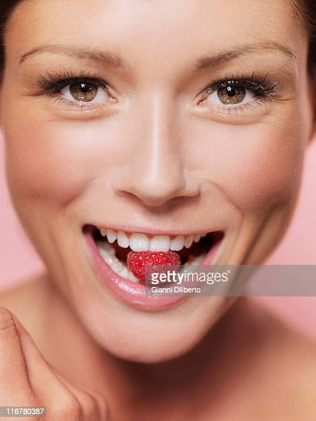 A woman holding a raspberry between her teeth, close-up