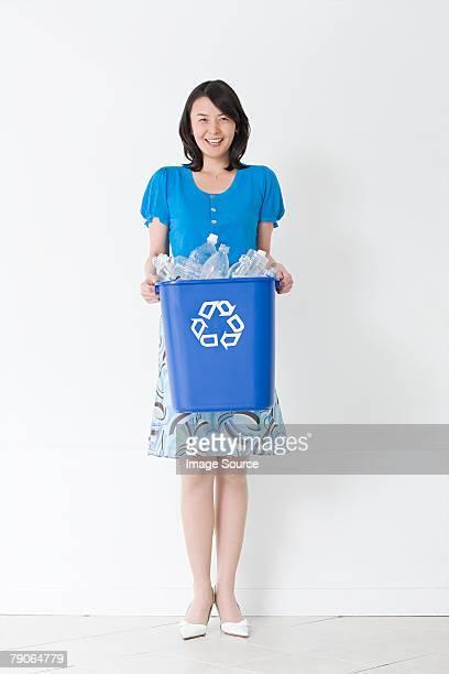 Une femme tenant une poubelle de recyclage
