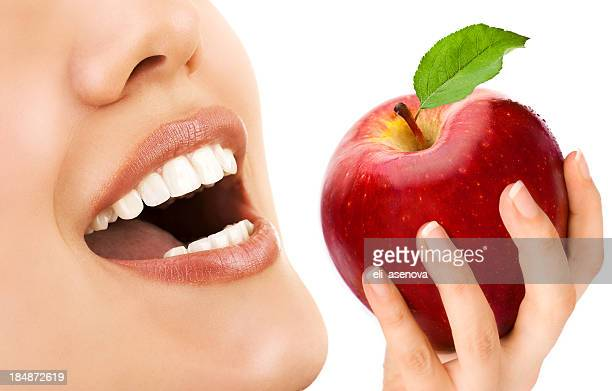 Woman holding a red apple with mouth open