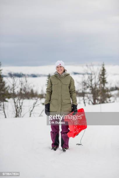Woman holding a red plastic sledge