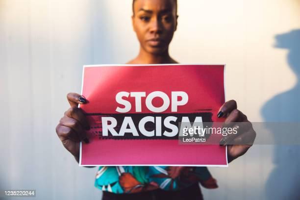 frau mit rotem schild wieder rassismus - antirassismus stock-fotos und bilder