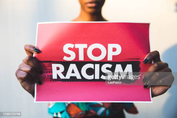 woman holding a red sign agains racism - anti racism stock pictures, royalty-free photos & images
