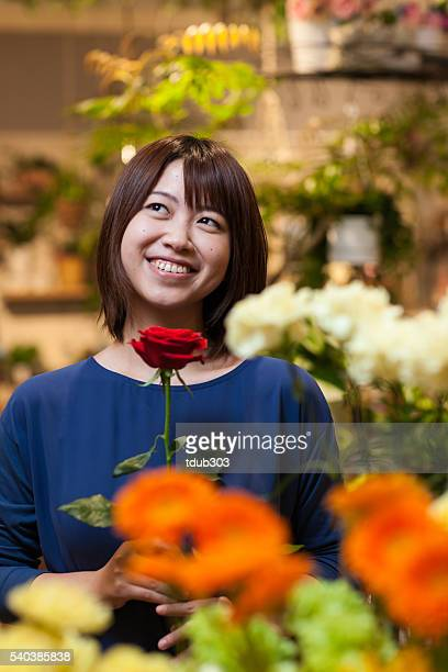 Woman holding a rose in a flower shop