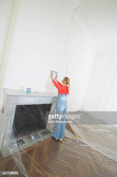 Woman Holding a Ruler Against a Wall