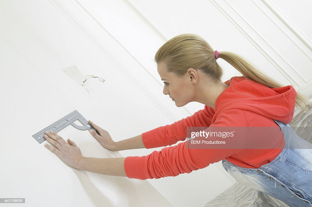Woman Holding a Ruler Against a Wall : Stock Photo