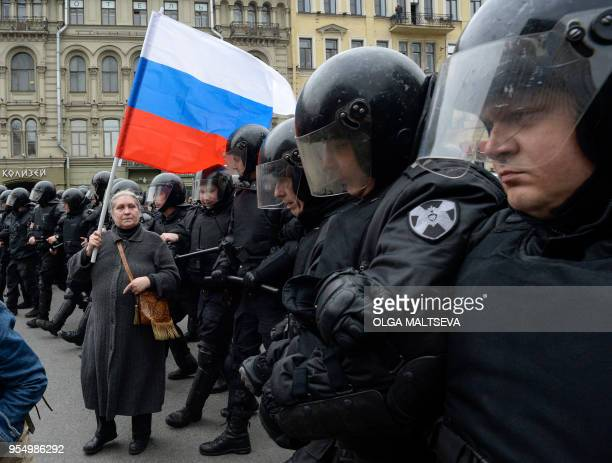 A woman holding a Russian flag stands in front of riot police blocking an area during an unauthorized antiPutin rally called by opposition leader...