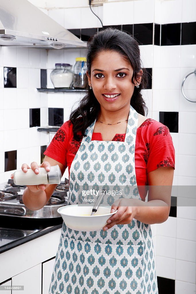 Woman holding a salt shaker and a bowl : Stock Photo