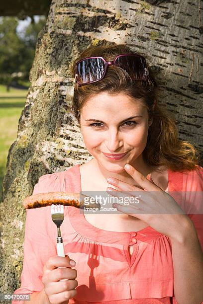 woman holding a sausage - snag tree stock pictures, royalty-free photos & images
