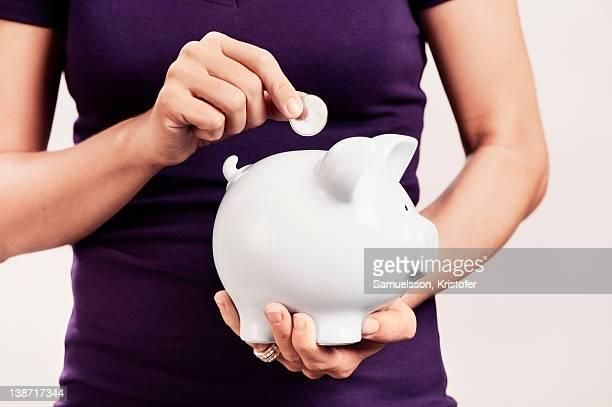 A woman holding a savings box