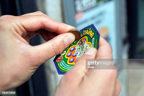 Woman holding a scratch card in her hands Winner winnings chance fate luck money